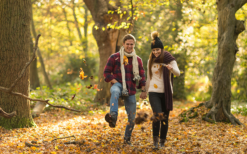 Two smiling friends or a couple kick leaves in the forest during a nature walk to beat the autumn blues