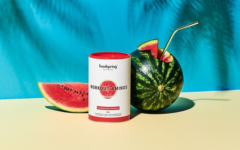 A canister of Workout Aminos sits next to a watermelon.