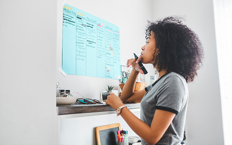 A woman of color looks thoughtfully at a blue wall planner divided into six columns, a great way to get on top of self-motivation