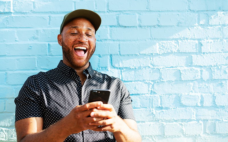 A freckled man of color in a baseball cap grins widely while staring at his phone. He's standing in front of a light-blue-washed brick wall.