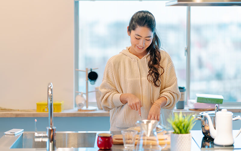 A woman of color stands in her kitchen, cutting something. We can't see what she's cutting, because there is a glass pitcher in the way, but she's smiling as she looks down at it. Her curly hair cascades over her left shoulder.