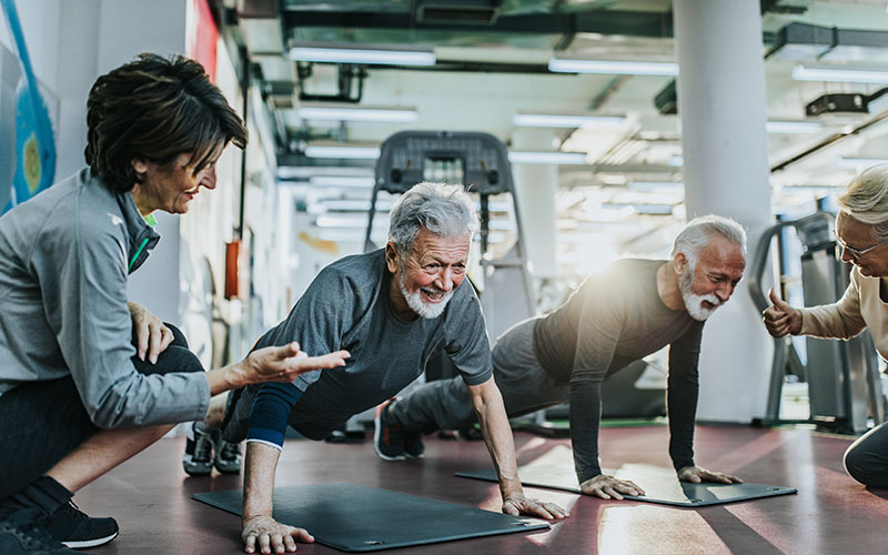 A group of older adults work out at a gym with equipment behind them. Find a gym that's right for you, like they have.