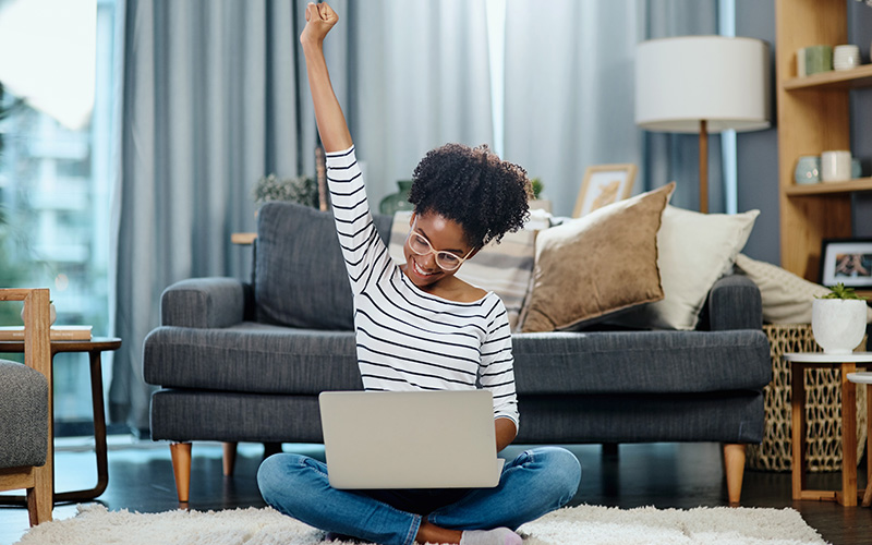 A woman of color sits on the carpet in front of a couch indoors. She's got a silver laptop on her lap and is raising one fist into the air, celebrating the results of successful self-motivation